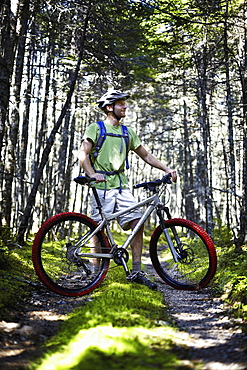 A mountain biker in a helmet with a rucksack standing by his bicycle in woodland, Cape Breton Island, Nova Scotia, Canada