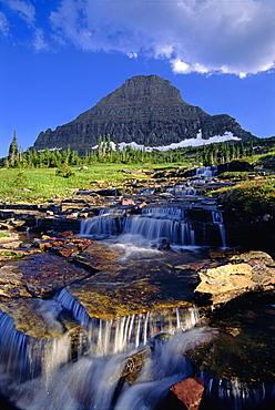 The landscape of Glacier National Park, to Mount Reynolds peak, and Logan Pass. Water flowing over rocks, Glacier National Park, Montana, USA