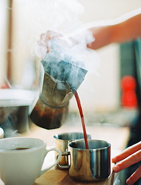 A person holding a coffee perculator and pouring hot coffee into cups, England