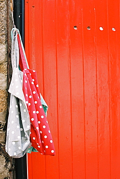 A vividly painted orange door, and two spotted cloth bags hanging from a nail, England