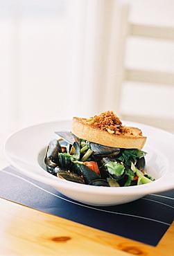 Mussels, shellfish on a white china dish. Garnishes, England