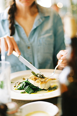 A woman eating a meal, a dish of fish and green vegetables, England