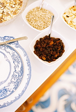 A tabletop with a blue and white plate, bowls of granola, oats and raisins, England