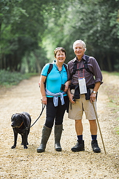 A mature couple hiking with their dog, England