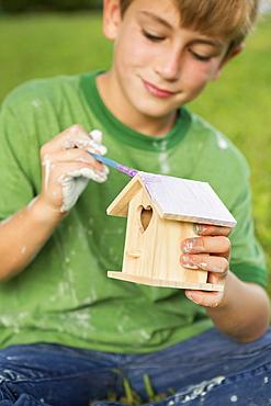 A boy in a garden, painting a bird houseAustin, Texas, USA