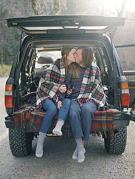 Young couple sitting in the back of their car, kissing, Millcreek, Utah, United States of America