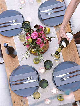 An apple orchard in Utah. A set table, a person pouring a glass of wine, Sataquin, Utah, United States of America