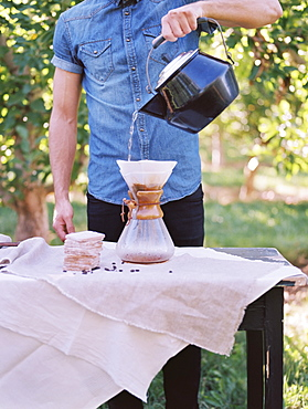 An apple orchard in Utah. man standing at a table, making coffee, Sataquin, Utah, United States of America
