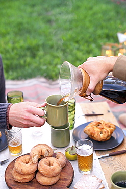 An apple orchard in Utah. Two people sitting at a table with food and drink, pouring coffee, Sataquin, Utah, United States of America