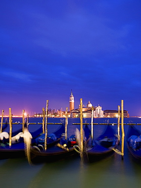 A view from the Riva degli Schiavoni and the Piazza San Marco across the water to the island and church of San Giorgio Maggiore, Gondolas moored at dusk, Venice, Italy