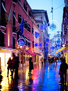 People walking in a narrow street at night, Street lights and decorations, Venice, Italy