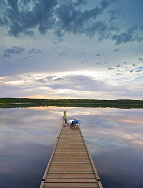 A couple, man and woman sitting at the end of a long wooden dock reaching out into a calm lake, at sunset, Canada