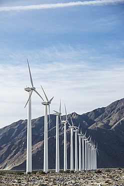 Wind power turbines in the landscape. A large number of turbine powers on a plain against a mountain backdrop, United States of America