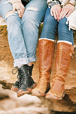 Close up of two women wearing leather boots sitting on a rock in a desert.