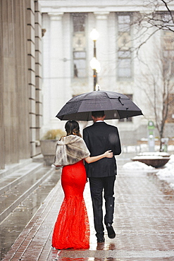 A woman in a long red evening dress with fishtail skirt and a fur stole, and a man in a suit, walking through a city.