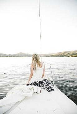 Blond teenage girl sitting on sail boat.