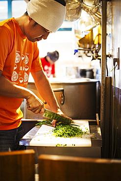 The ramen noodle shop. A chef chopping vegetables, Japan
