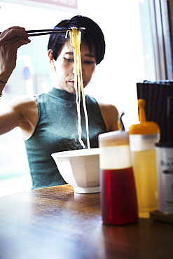 A ramen noodle cafe in a city. A woman seated eating a ramen noodle dish using chopsticks, Japan