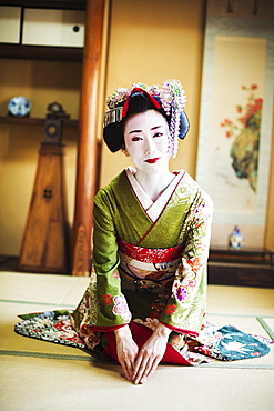 A woman dressed in the traditional geisha style, wearing a kimono and obi, with an elaborate hairstyle and floral hair clips, with white face makeup with bright red lips and dark eyes. Kneeling on the floor, Japan