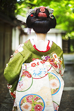 A woman dressed in the traditional geisha style, wearing a kimono and obi, with an elaborate hairstyle and floral hair clips, with white face makeup with bright red lips and dark eyes on a street, Japan