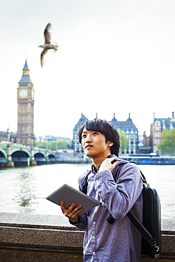 Young Japanese man enjoying a day out in London, standing on the Queen's Walk by the River Thames, United Kingdom