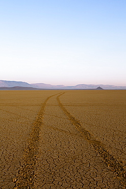 Tyre tracks in a desert landscape with mountains in the distance.