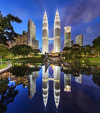 Illuminated Petronas Towers building in Kuala Lumpur, Malaysia at dusk, Reflection in lake, Kuala Lumpur, Malaysia