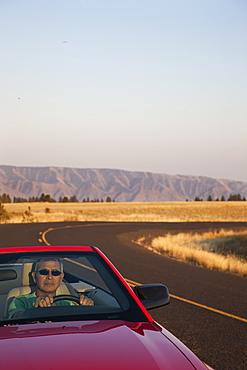 A senior Hispanic man at the wheel of his convertible sports car, United States of America
