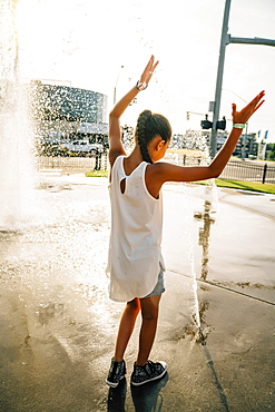Girl playing in public fountain in summer, United States of America