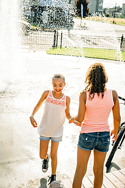 Smiling girls playing in public fountain in summer, United States of America