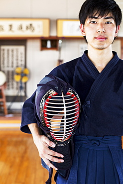 Male Japanese Kendo fighter standing in a gym, holding Kendo mask, looking at camera, Kyushu, Japan