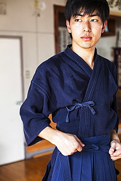 Male Japanese Kendo fighter tying belt of his blue Kendo uniform, Kyushu, Japan