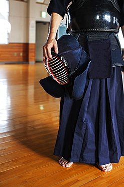 Male Japanese Kendo fighter standing in a gym, holding Kendo mask, Kyushu, Japan