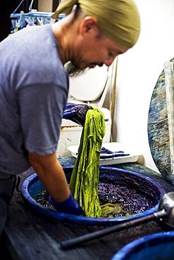 Japanese man wearing bandana standing in a textile plant dye workshop, dyeing piece of green fabric, Kyushu, Japan