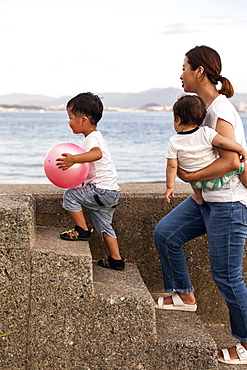 Japanese woman carrying toddler and young boy with pink ball walking up concrete steps by the ocean, Kyushu, Japan