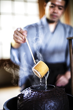 Close up of traditional Japanese Tea Ceremony, man using a Hishaku, a bamboo ladle, to pour hot water, Kyushu, Japan