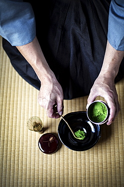 High angle close up of traditional Japanese Tea Ceremony, man spooning green Matcha tea powder into bowl, Kyushu, Japan
