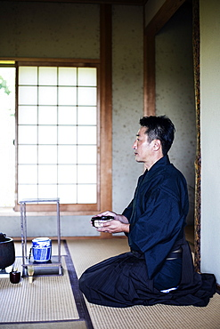 Japanese man wearing traditional kimono kneeling on floor, holding tea bowl, during tea ceremony, Kyushu, Japan