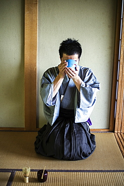 Japanese man wearing traditional kimono kneeling on floor, raising blue tea bowl during tea ceremony, Kyushu, Japan