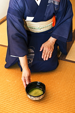 High angle view of Japanese woman wearing traditional bright blue kimono with cream coloured obi kneeling on floor, holding bowl with Matcha tea, Kyushu, Japan
