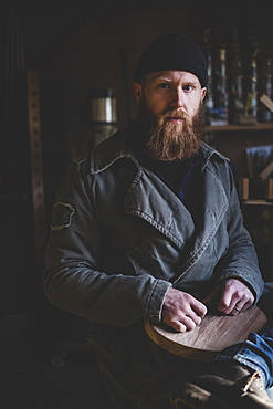 Bearded man wearing black beanie sitting in workshop, holding piece of wood, looking at camera, Berkshire, England