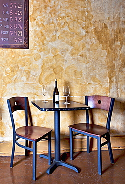 Bottle of wine and glasses on table in wine bar, Oregon, Washington, USA