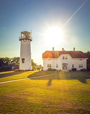 Home and lighthouse on rural lawn