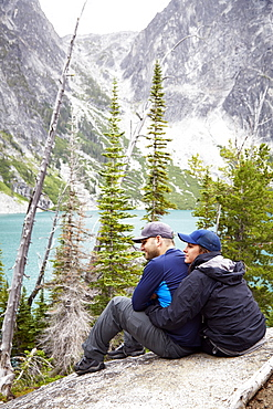 Couple admiring mountains and remote lake, Leavenworth, Washington, USA