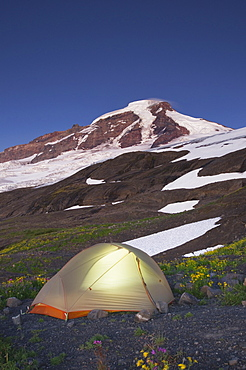 Glowing tent at campsite in remote landscape, North Cascades, Washington, USA