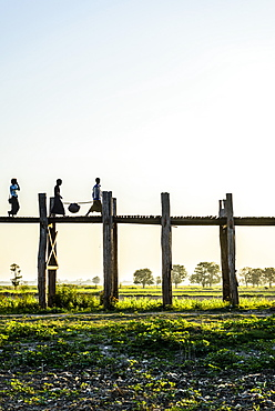 People walking on elevated wooden walkway in rural landscape, Myanmar, Burma