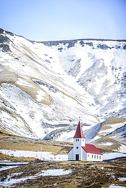 Church under snowy mountains in rural landscape, Vik, Iceland