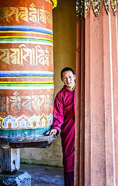 Asian monks standing by pillar in temple, Bhutan, Kingdom of Bhutan