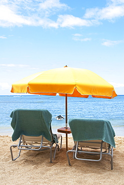 Lawn chairs and umbrella on beach, Honolulu, Oahu, USA