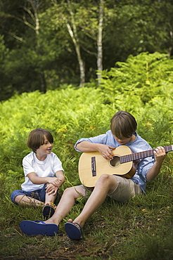 Two boys camping in New Forest. Sitting on the grass, one playing a guitar, Hampshire, England